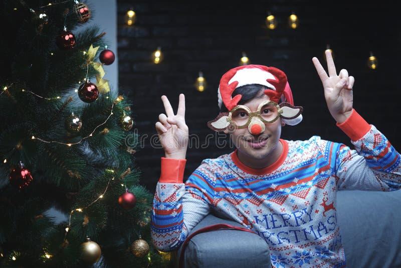 亚裔坐B的人佩带的圣诞节驯鹿玻璃红色鼻子 免版税图库摄影