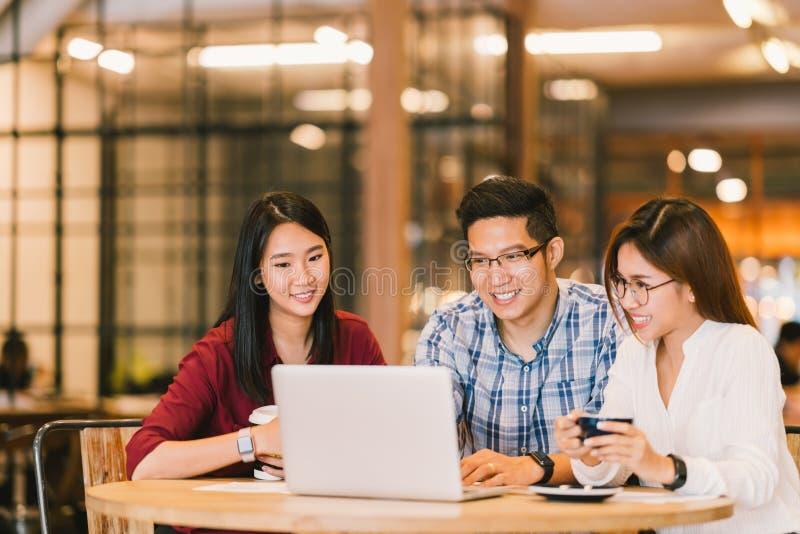 亚裔大学生一起使用便携式计算机的小组或工友在咖啡馆或大学 偶然事务,做自由职业者工作 库存图片