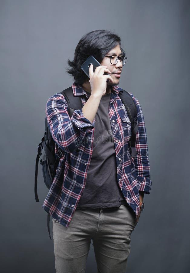 亚裔大学生拾起在灰色背景的手机 免版税库存照片
