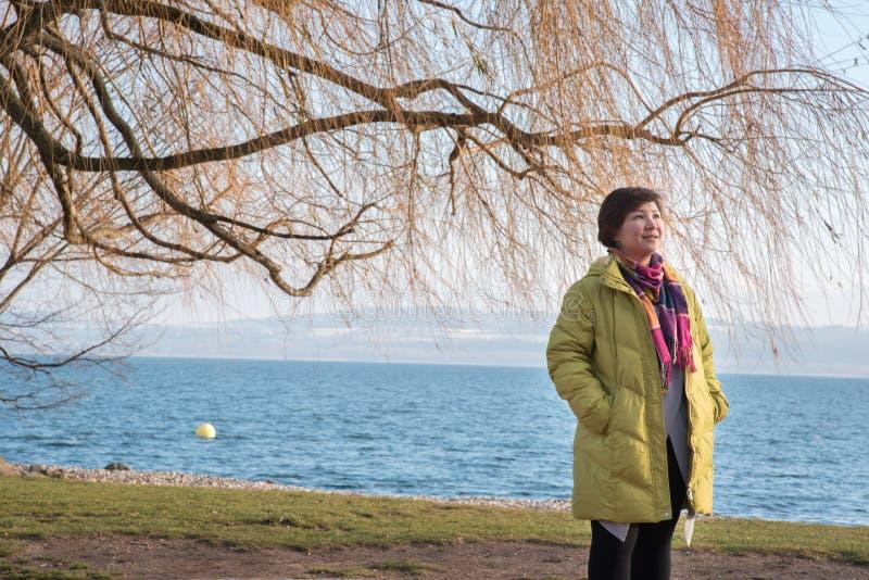亚裔夫人旅行家,纳沙泰尔镇在冬天,瑞士,欧洲 免版税库存照片