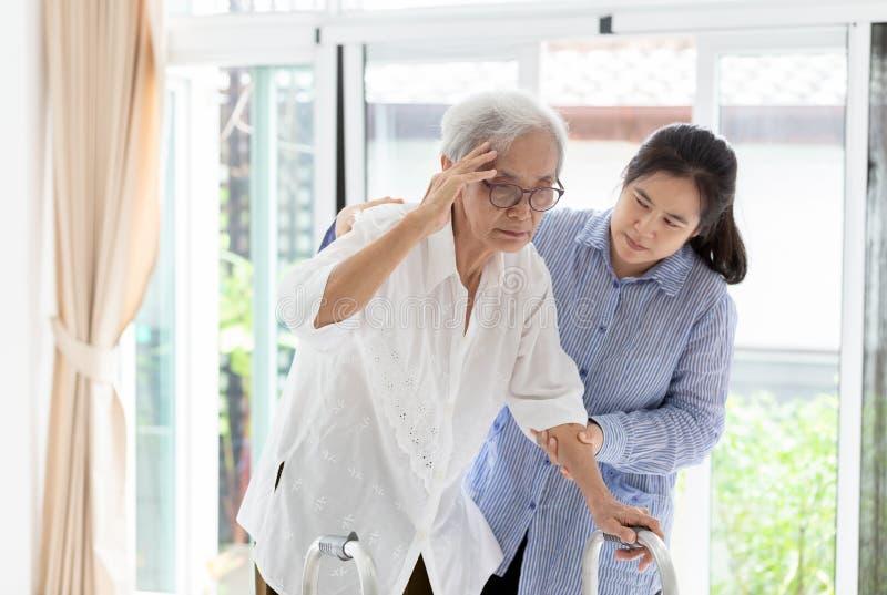 亚裔女儿或关心辅助帮助的支持资深妇女或母亲,传达眩晕的症状;头晕;偏头痛; 免版税库存照片