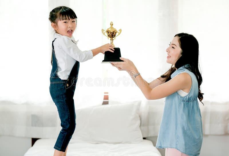 亚裔女儿表达激发,在得到奖励作为战利品从她的母亲后,并且她在白色床上站立 库存图片