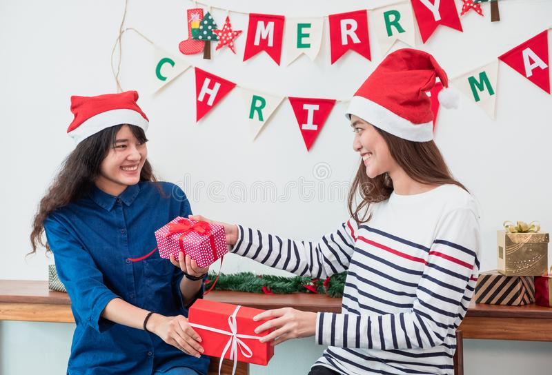 亚裔女友佩带在圣诞快乐的帽子集会和e的圣诞老人 库存照片