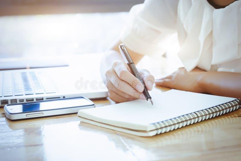 亚裔女商人在空白的笔记本写笔记 库存图片