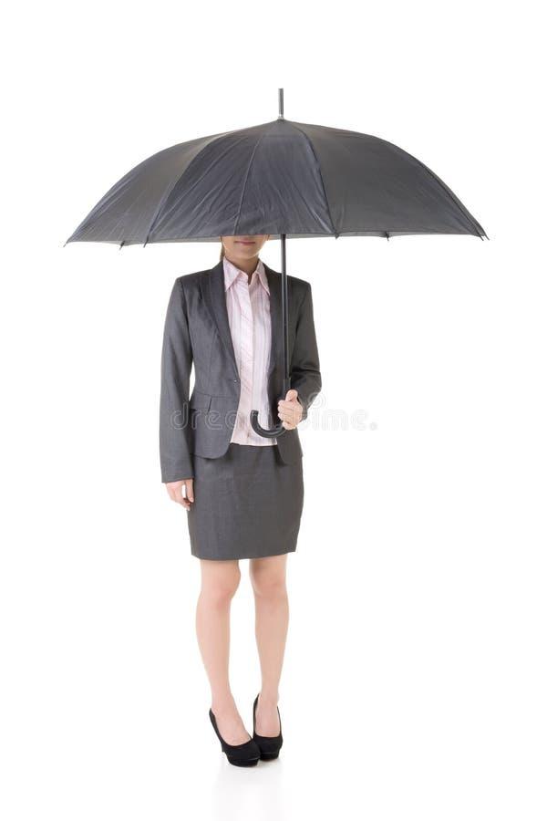 亚裔女商人拿着伞。 库存照片