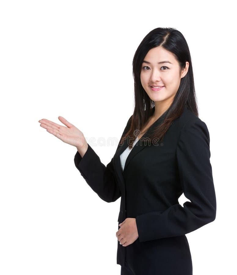 亚裔女商人用手介绍某事 库存照片