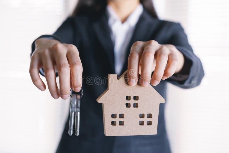 亚裔女商人的手拿着钥匙和式样房子 免版税库存图片