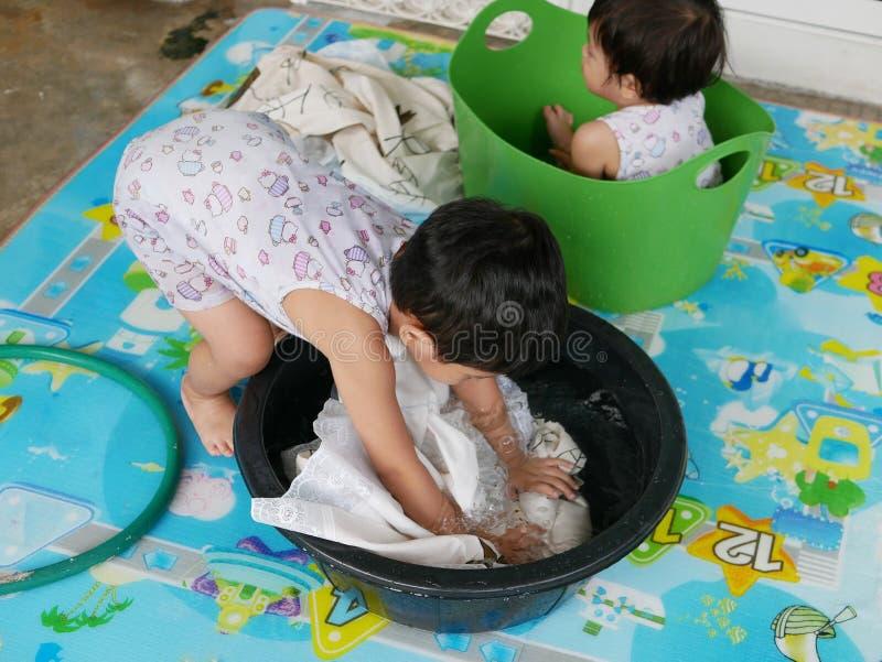 亚裔女婴在水中把浸泡的衣裳留在家洗涤它 免版税库存图片