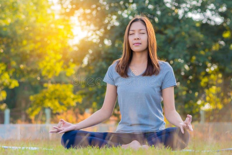 年轻亚裔女子实践的瑜伽,坐在容易的姿势在公园 库存图片