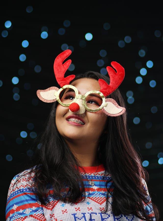 亚裔女孩佩带的圣诞节毛线衣和圣诞节驯鹿Glas 库存照片