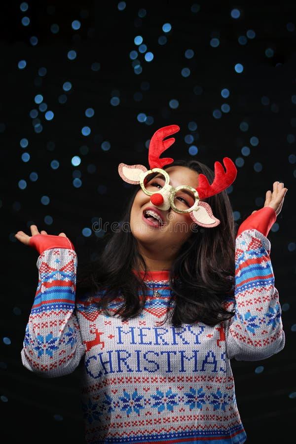 亚裔女孩佩带的圣诞节毛线衣和圣诞节驯鹿Glas 库存图片
