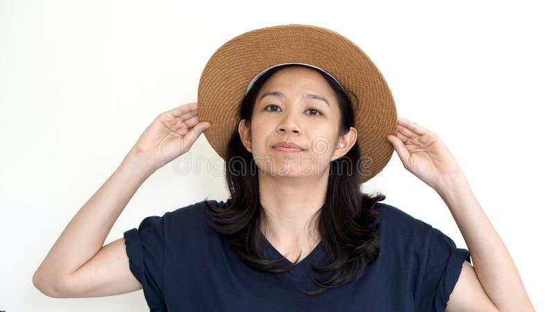 亚裔女孩佩带的帽子和偶然衬衣,微笑和愉快在丝毫 免版税库存照片