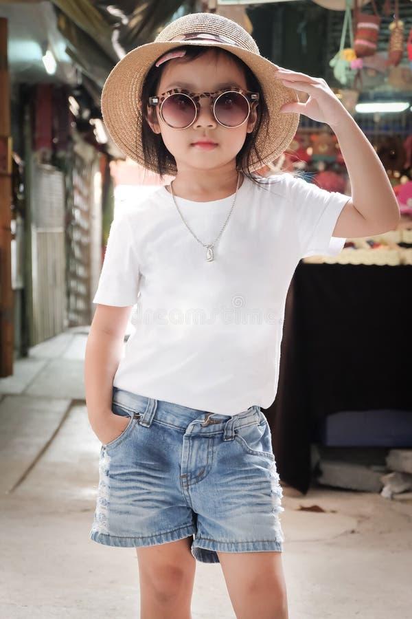 亚裔女孩佩带的白色T恤杉姿势时尚 库存照片