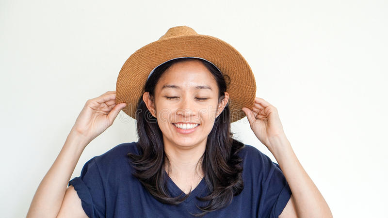 亚裔女孩佩带的草帽夏天乐趣 放松,并且愉快表达 免版税库存图片