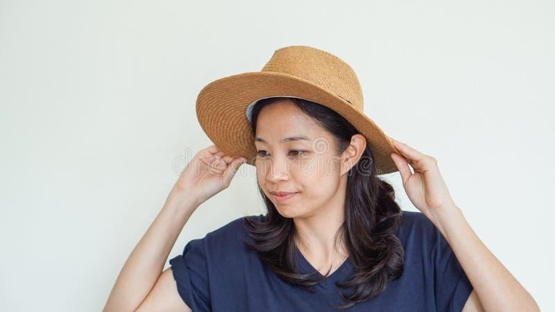 亚裔女孩佩带的草帽夏天乐趣 放松,并且愉快表达 图库摄影