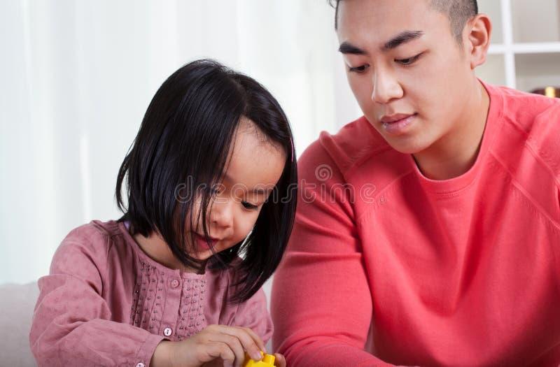 亚裔女孩和有同情心的爸爸 免版税库存图片