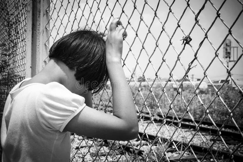 亚裔女孩哀伤的单独手举行监狱 库存照片