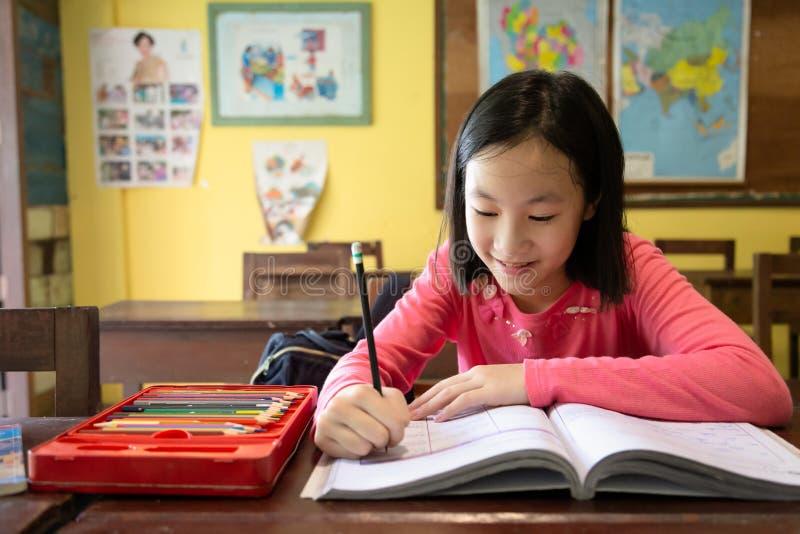亚裔女孩喜欢学习在教室,学习一名微笑的儿童的学生的画象举行在书的铅笔文字,坐 免版税库存照片