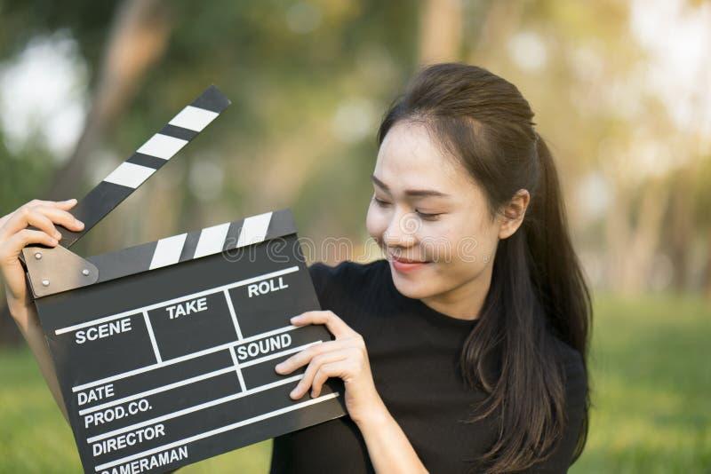 亚裔女孩在她的手上的拿着拍板 库存照片