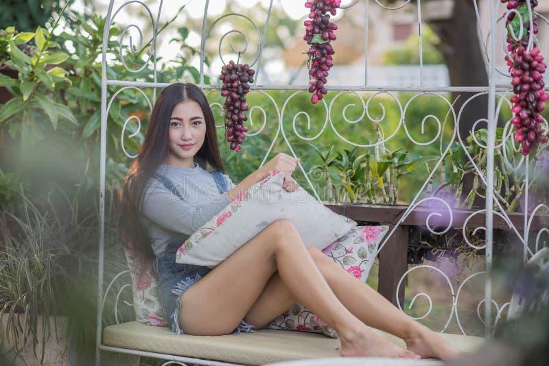 亚裔女孩坐沙发,放松 库存照片