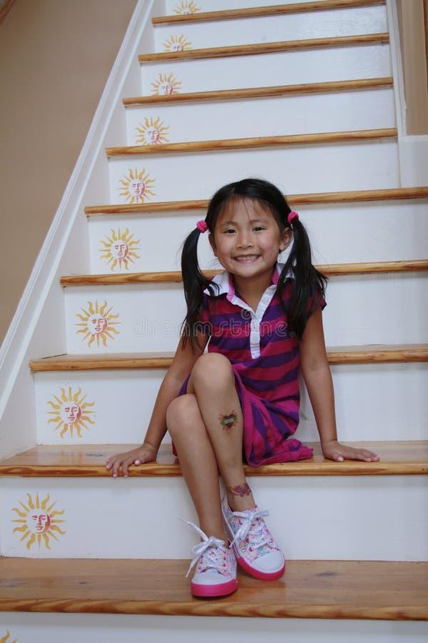 亚裔女孩坐的步骤 免版税图库摄影