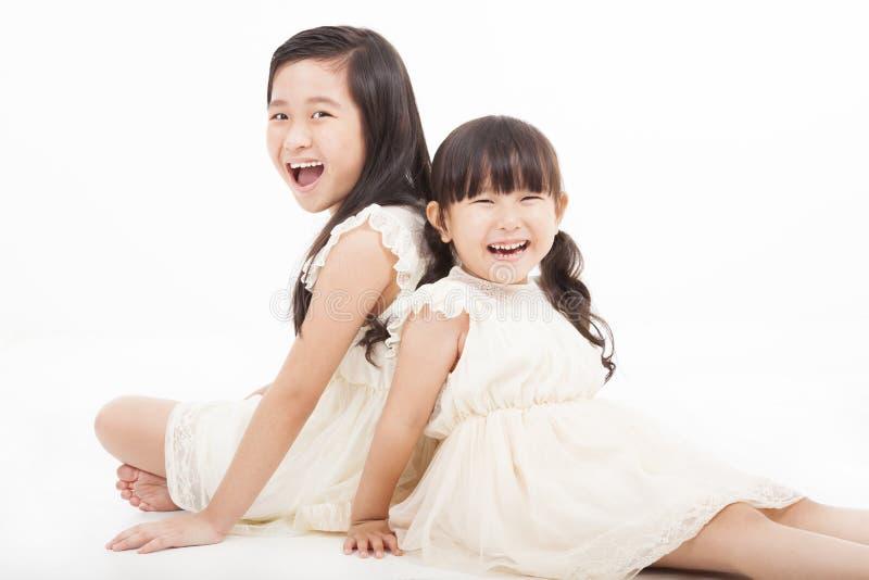 亚裔女孩坐空白背景 免版税库存照片