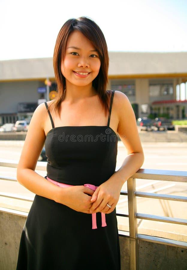亚裔女孩室外俏丽的微笑身分 免版税库存图片