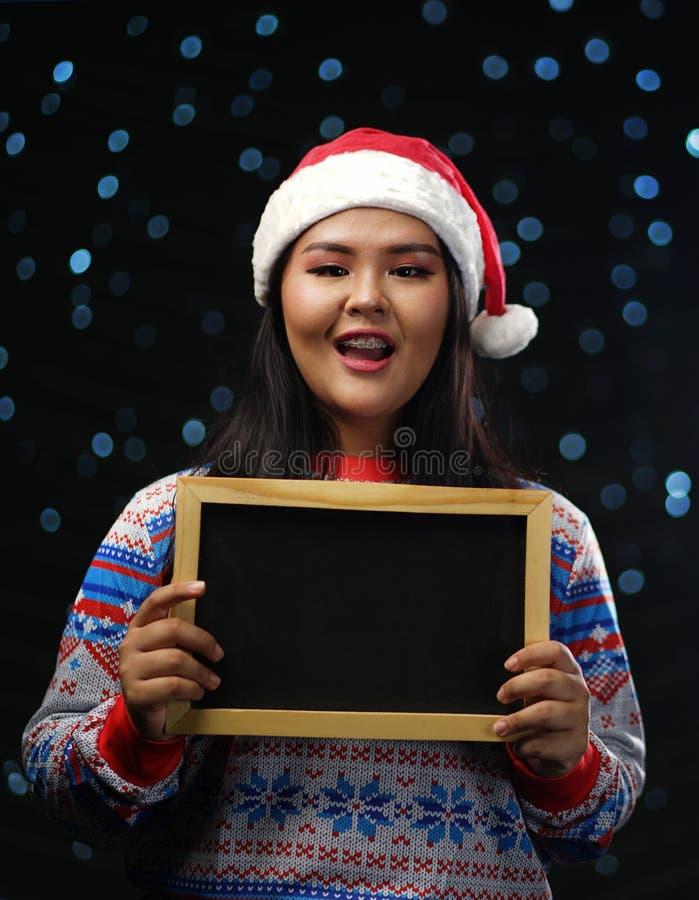 亚裔女孩小佩带的圣诞节毛线衣和圣诞老人的帽子对负 库存图片