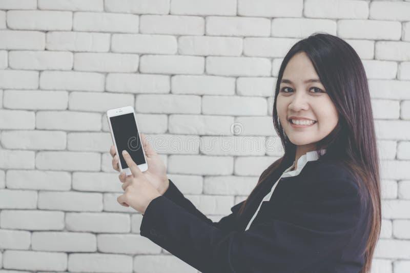亚裔女孩微笑并且使用她的手指向智能手机、背景白色砖墙、网上贸易的概念和拍卖 库存图片