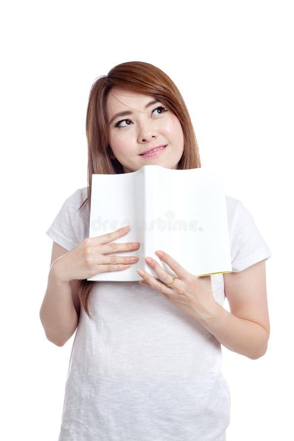 亚裔女孩想象并且微笑与书 库存图片
