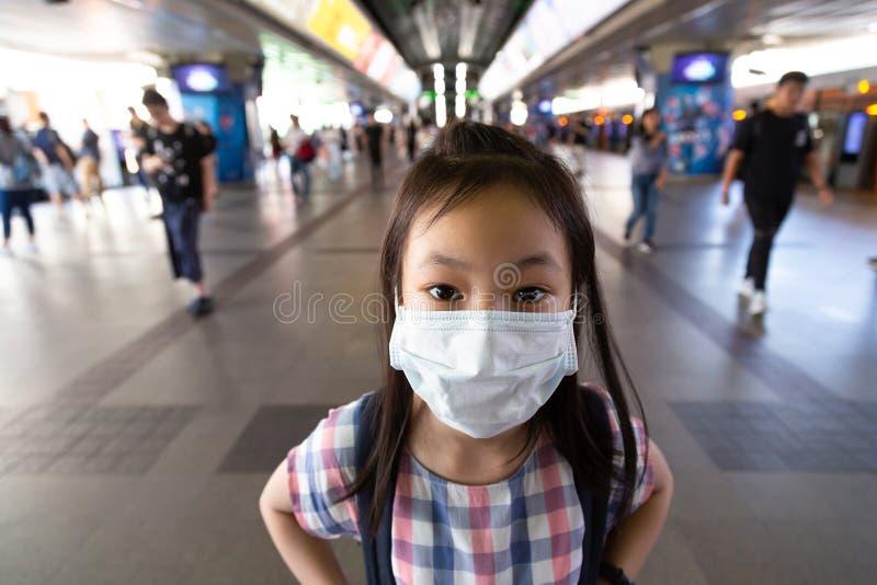 亚裔女孩戴着在peop人群的白色防毒面具  库存照片