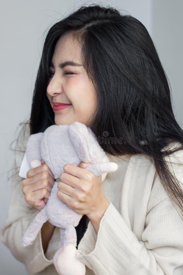 亚裔女孩拥抱她的玩偶 免版税库存图片