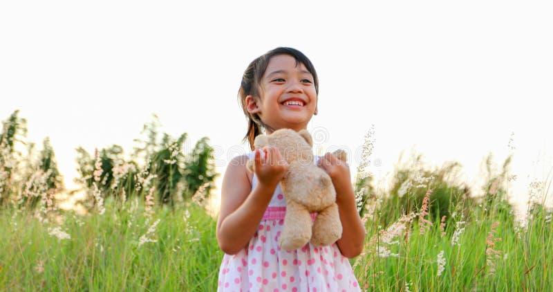 亚裔女孩演奏玩具熊的和笑愉快在草甸在夏天本质上 库存图片