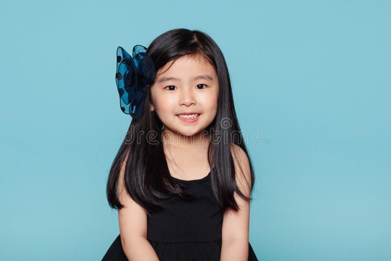 亚裔女孩演播室画象有愉快的神色的在蓝色背景前面 库存图片