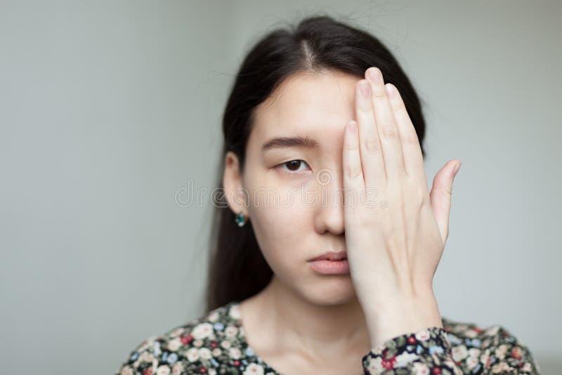 亚裔女孩用手报道一半她的面孔 在她的面孔的哀伤的神色 免版税图库摄影