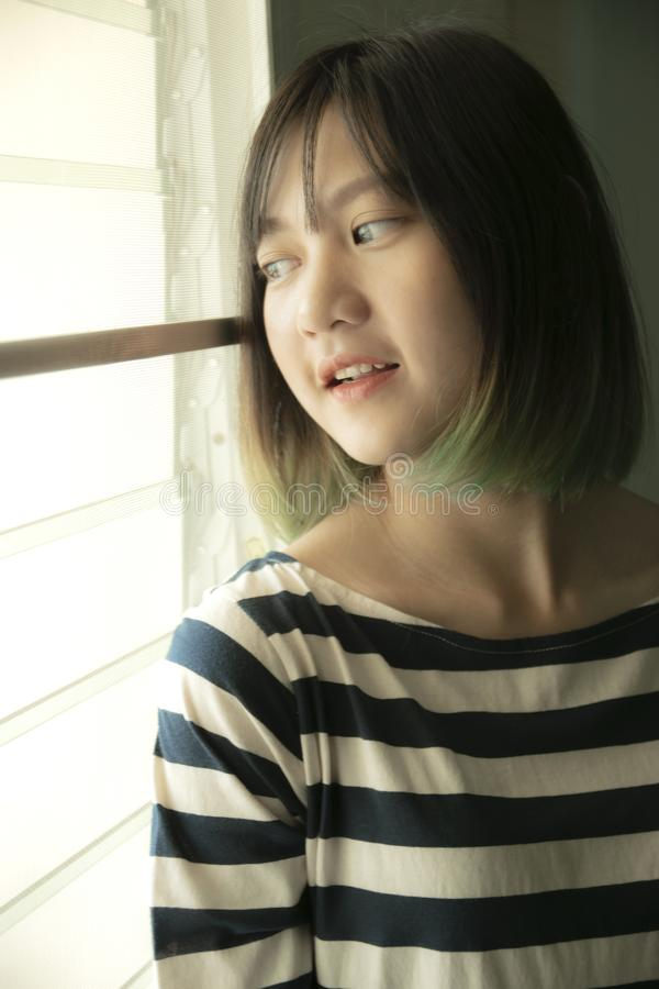 亚裔女孩画象有看的某处从窗口 免版税库存图片