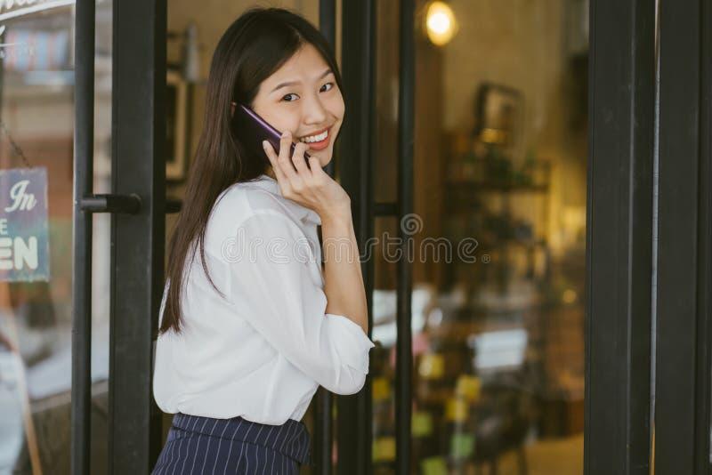 亚裔女孩画象进入门到咖啡馆 使用电话的女实业家和走到咖啡馆 免版税库存照片