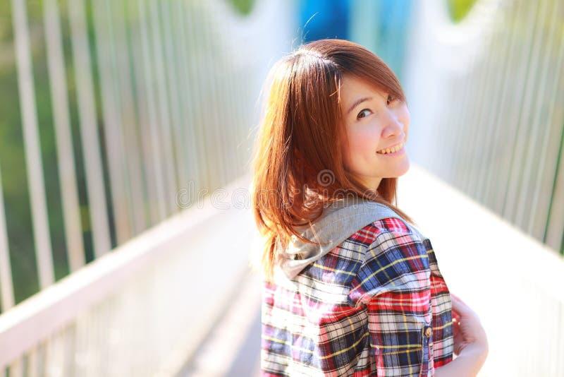亚裔女孩的特写镜头画象摆在户外穿戴格子花呢上衣的20岁 免版税图库摄影