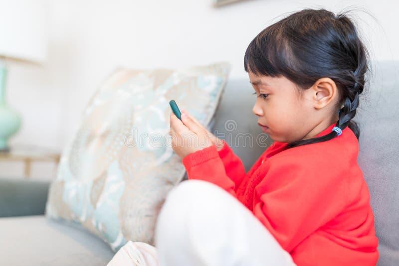 亚裔女孩看巧妙的电话和坐沙发 免版税图库摄影
