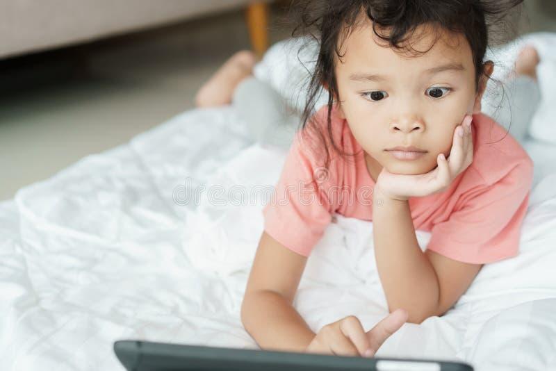 亚裔女孩观看在网上媒介令人激动的录影 女孩使用片剂注意录影家 免版税库存照片