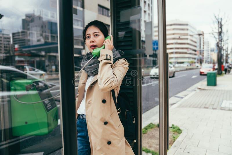 亚裔女孩谈话在公开投币式公用电话户外 免版税库存照片
