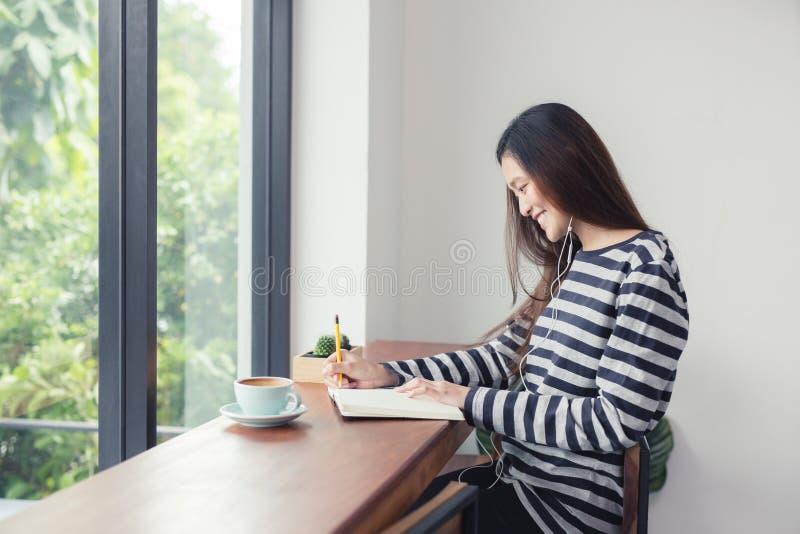 亚裔女孩采取笔记并且听到在咖啡的音乐 免版税库存图片