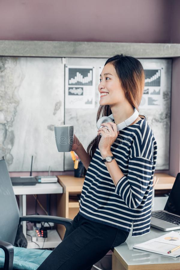 亚裔女实业家在采取咖啡休息与smili一起使用以后 库存图片