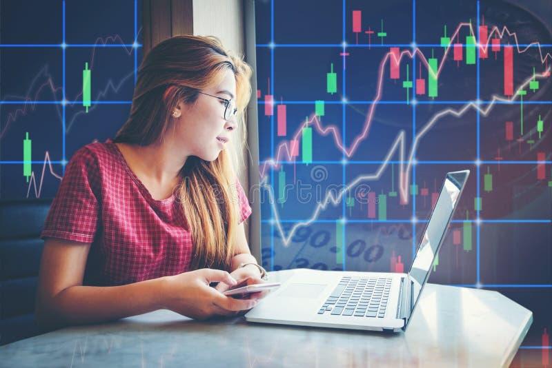亚裔女实业家坐的和运作的膝上型计算机股市exch 库存图片