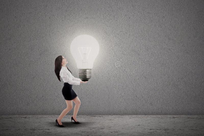 亚裔女实业家运载电灯泡 图库摄影