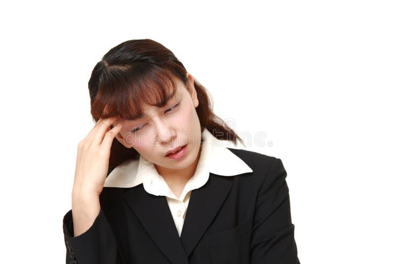 亚裔女实业家遭受头疼 免版税库存照片