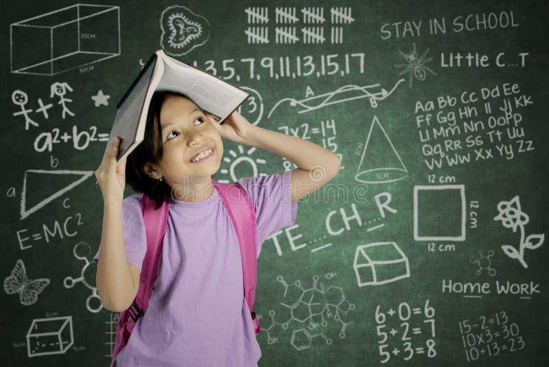 亚裔女小学生在她的头上把一本开放书放 库存图片