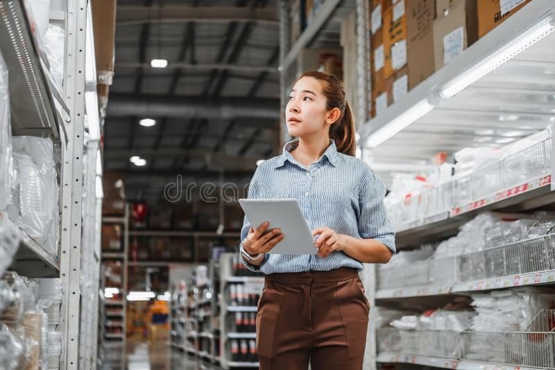 亚裔女工与数字片剂复选框后勤进口一起使用和出口供应包裹在仓库里, 库存照片