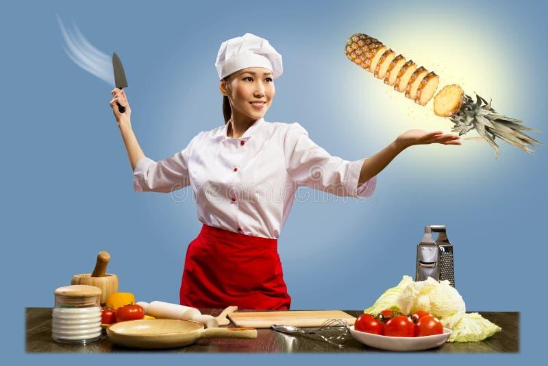 亚裔女性主厨切菠萝 免版税库存图片
