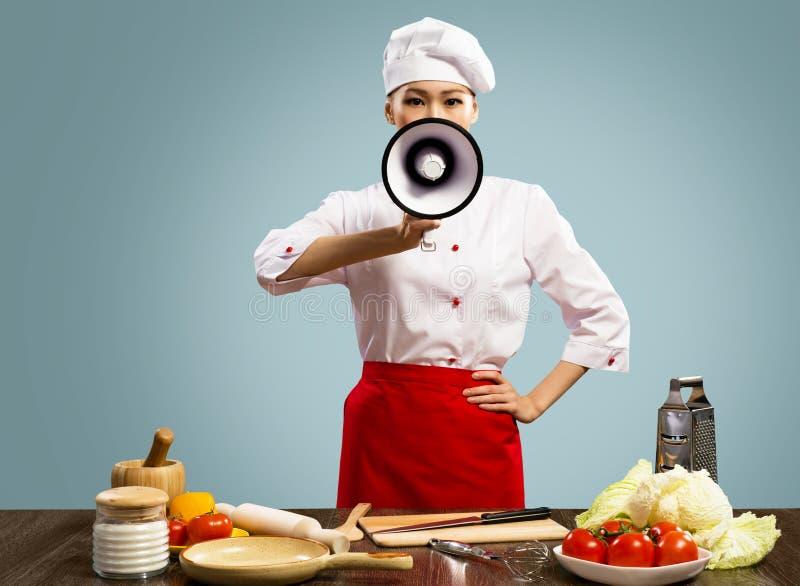 亚裔女性主厨拿着一台扩音机 免版税库存图片